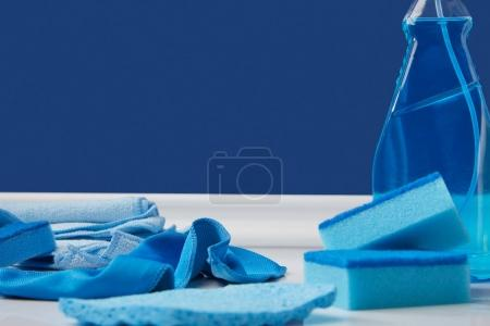 blue spray, rags and washing sponges for spring cleaning on floor