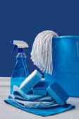 rags, bucket and spray for spring cleaning on blue