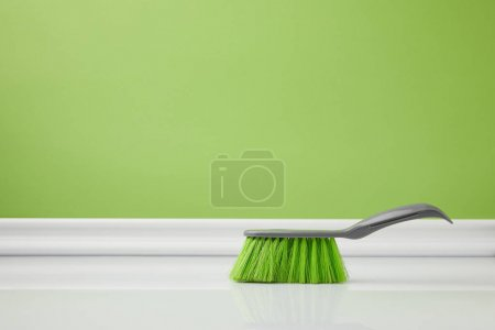 Photo for Green brush for spring cleaning on white floor - Royalty Free Image