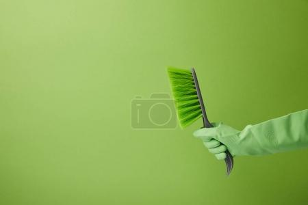 cropped image of man holding brush for spring cleaning isolated on green
