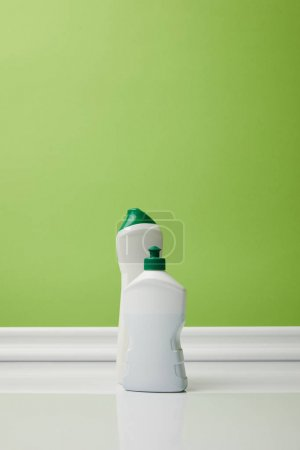 bottles with domestic supplies for spring cleaning on green