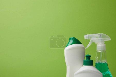 Photo pour Bouteilles et vaporisateur pour le nettoyage de printemps isolé sur vert - image libre de droit