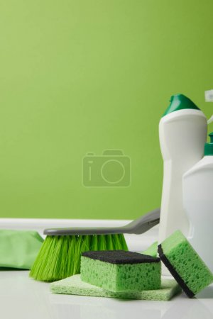 Photo for Green brush, washing sponges and bottles of liquids for spring cleaning - Royalty Free Image