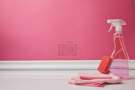 pink washing sponge, rags and spray for spring cleaning