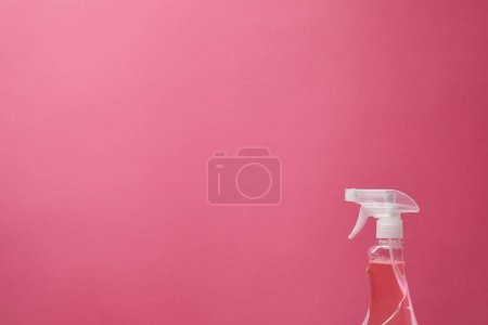 spray bottle with antiseptic liquid isolated on pink