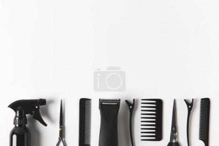 Photo pour Vue de dessus de tondeuse à cheveux et outils de coiffure en rangée, sur blanc - image libre de droit