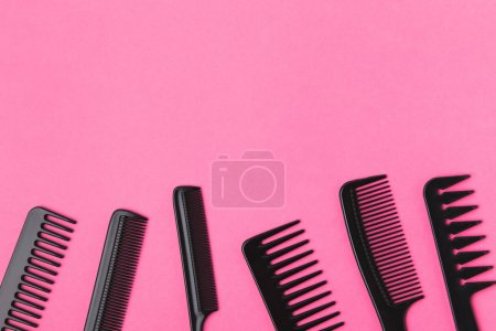 top view of black combs, isolated on pink