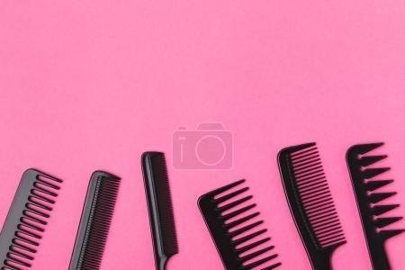 Photo pour Vue de dessus des peignes noirs, isolés sur rose - image libre de droit