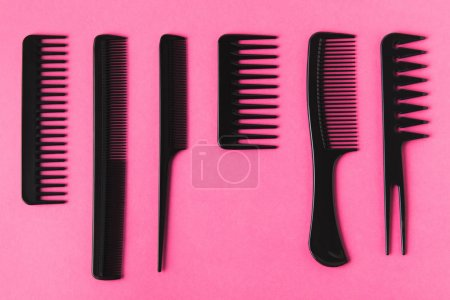 top view of black hair combs, isolated on pink