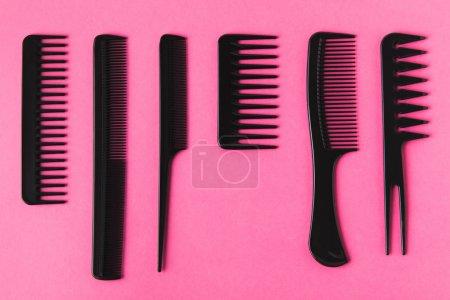 Photo pour Vue de dessus des peignes de cheveux noirs, isolés sur rose - image libre de droit