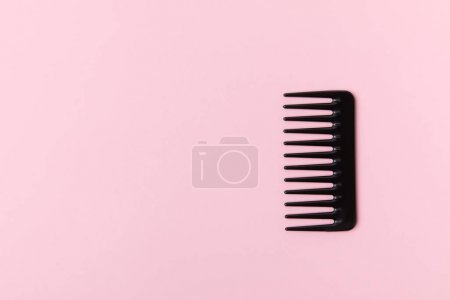 one black comb, isolated on light pink