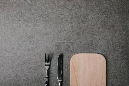 top view of wooden board with fork and knife on grey background