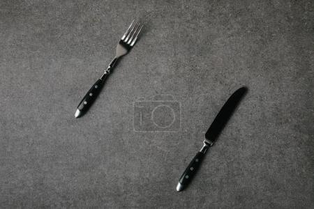 top view of fork and knife on grey background