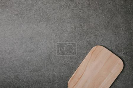 top view of empty wooden cutting board on grey background