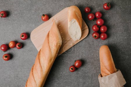 top view of baguettes, wooden board and fresh tomatoes on grey