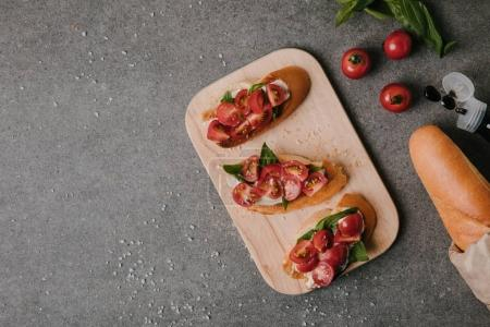 top view of tasty tomato bruschetta on wooden board and fresh ingredients on grey