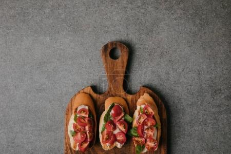 top view of gourmet italian bruschetta on wooden cutting board on grey