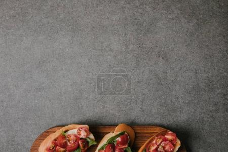 top view of delicious italian bruschetta on wooden board on grey background