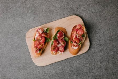 top view of gourmet italian bruschetta on wooden board on grey