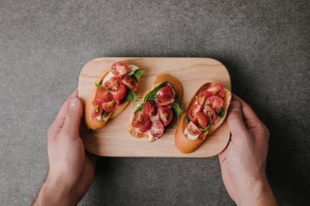 cropped shot of person holding wooden board with delicious tomato bruschetta