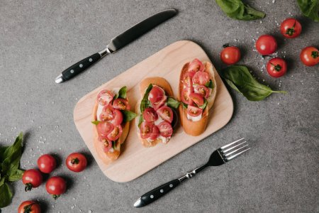 top view of tasty italian bruschetta on wooden board, ingredients and cutlery on grey