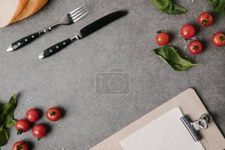 top view of fork and knife, blank clipboard, baguette, basil and fresh tomatoes on grey