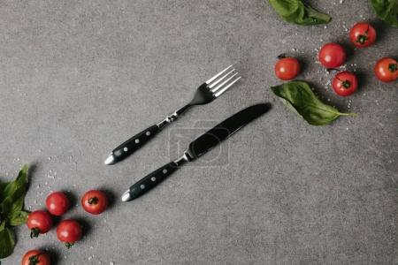 top view of fresh tomatoes, basil and salt with cutlery on grey