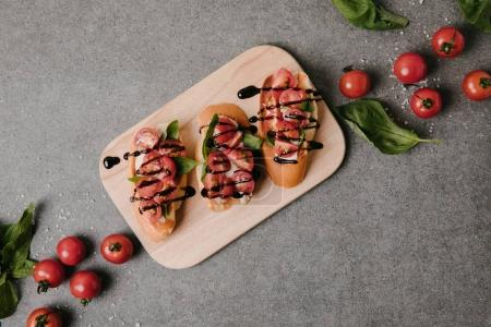 top view of traditional italian bruschetta on wooden board with basil and fresh tomatoes on grey