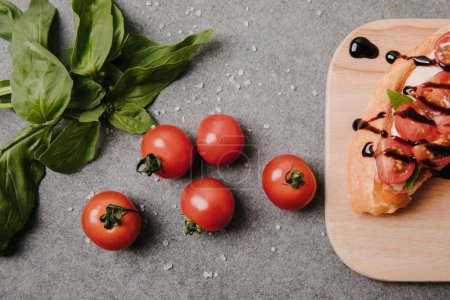top view of delicious bruschetta on wooden board, basil and fresh tomatoes on grey