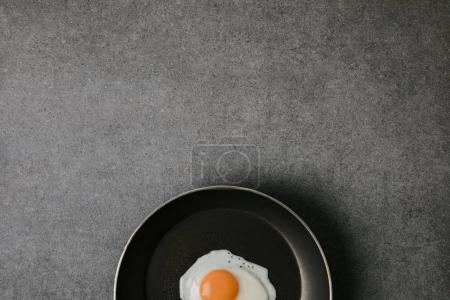 top view of frying pan with tasty fried egg on grey background