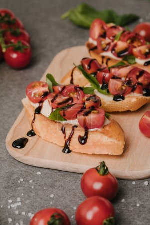 close-up view of tasty healthy bruschetta with tomatoes and balsamic on wooden board
