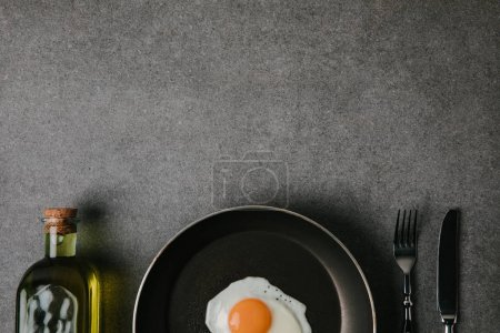 top view of frying pan with fried egg, cutlery and bottle of oil on grey