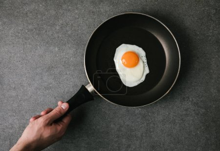 partial top view of person holding frying pan with fried egg on grey