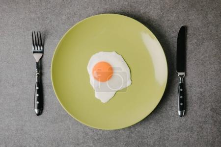 top view of tasty fried egg on plate and fork with knife on grey