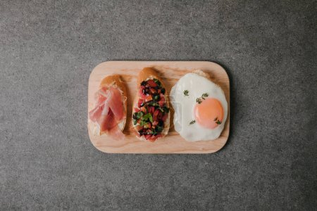 top view of delicious antipasto bruschetta with fried egg on wooden board on grey