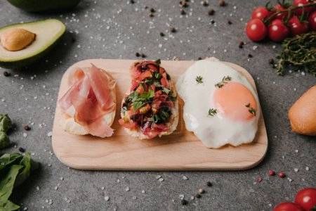 antipasto bruschetta and fried egg on wooden cutting board and ingredients on grey