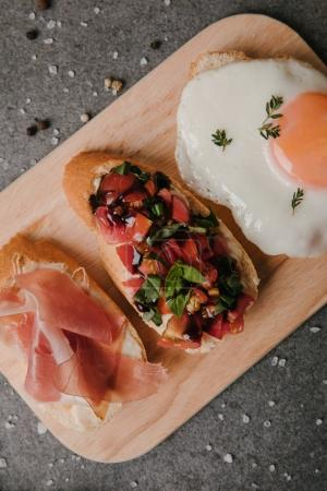 delicious antipasto bruschetta and fried egg on wooden cutting board and spices on grey