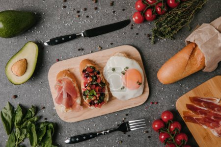top view of gourmet antipasto bruschetta and fried egg on wooden cutting board
