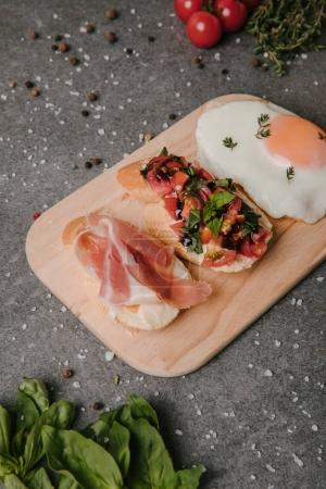 gourmet antipasto bruschetta and fried egg on wooden cutting board