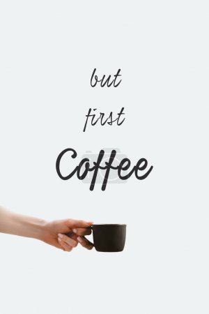 """cropped view of hand holding black cup of coffee, isolated on white with """"But first coffee"""" lettering"""