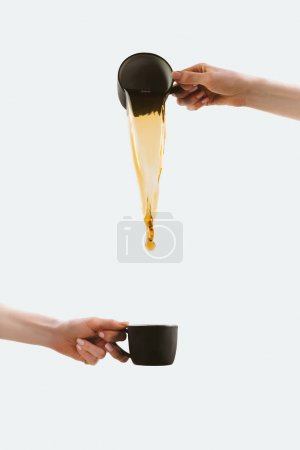 Photo for Cropped view of hands pouring coffee from one cup into other, isolated on white - Royalty Free Image