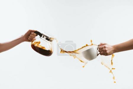 Photo pour Vue recadrée de personne tenant la tasse et verre pot avec des touches de café, isolé sur blanc - image libre de droit