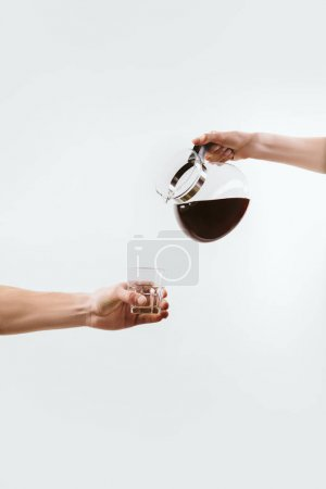 cropped view of hands with coffee pot and glass, isolated on white