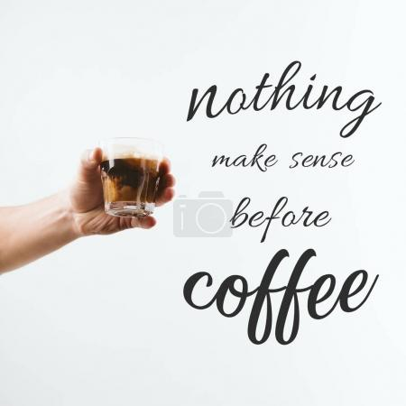 "Photo for Cropped view of hand holding glass full of coffee with milk, isolated on white with ""Nothing make sense before coffee"" inspiration - Royalty Free Image"