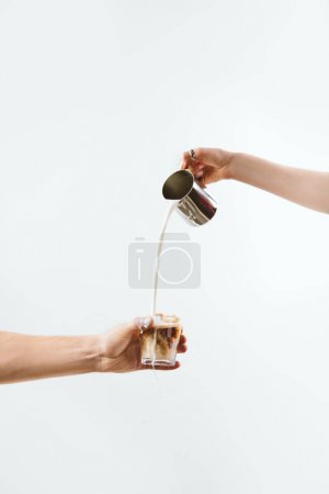 cropped view of hand pouring milk into glass with coffee, isolated on white