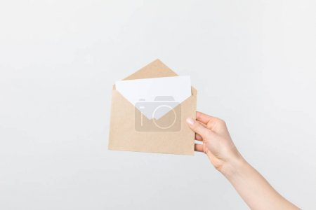 partial view of woman holding kraft envelope with blank card in hand isolated on white