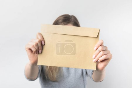 obscured view of woman showing blank kraft envelope in hands isolated on white
