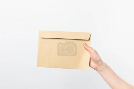partial view of woman holding blank kraft envelope in hand isolated on white