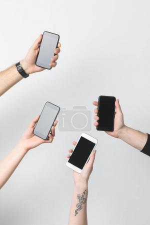 partial view of group of people with smartphones with blank screens isolated on white