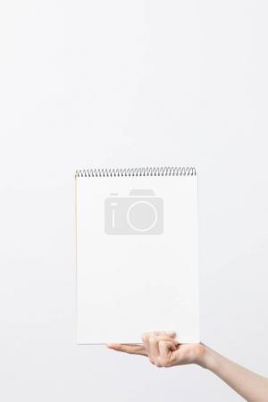 partial view of woman holding blank sketchbook in hand isolated on white